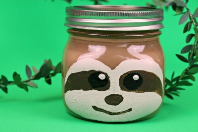 sloth painted mason jar on a green background