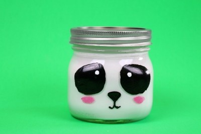 Panda painted mason jar on a green background