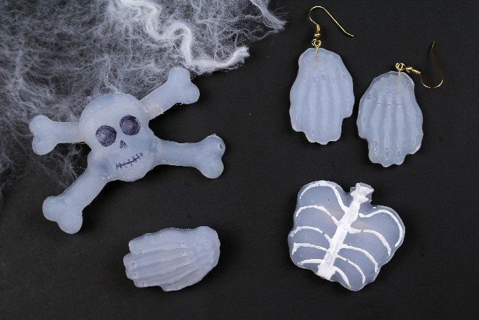 DIY glue gun skeleton jewelry on a black background