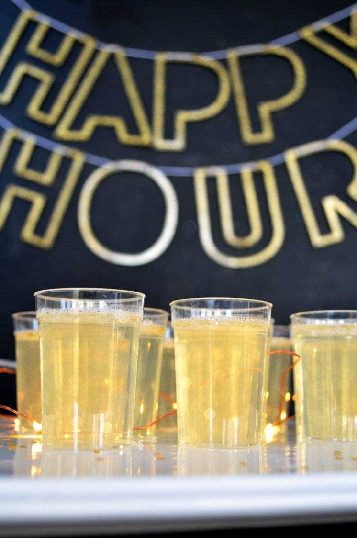champagne jello shots in front of a happy hour sign
