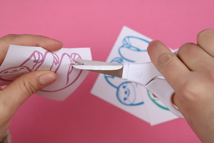 hands cutting sloth valentines with scissors