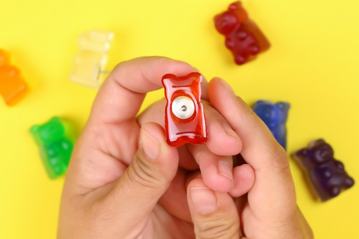 hands holding DIY gummy bear thumbtack