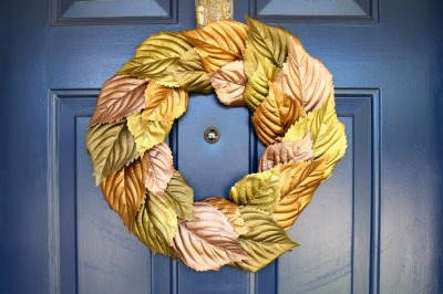 wreath made of metallic painted leaves on a blue door
