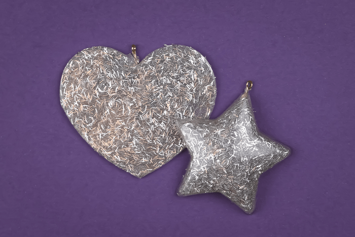 silver glitter resin ornaments on a purple background