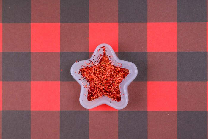 glitter resin in a star mold on a plaid background