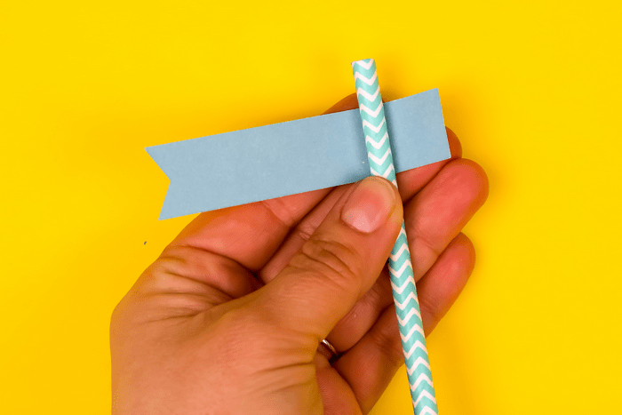 hand assembling a paper party straw flag