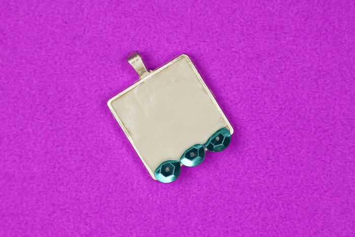 3 teal sequins embedded in jewelry clay in pendant bezel  on a purple background