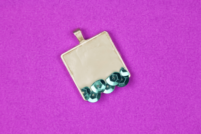 teal sequins embedded in jewelry clay in pendant bezel  on a purple background