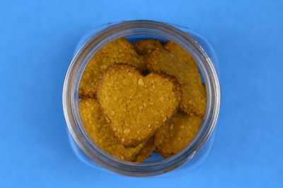 Mason jar with heart shaped homemade dog treats on blue background