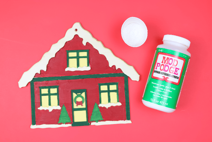 Painted Christmas house sign with Mod Podge on a red background