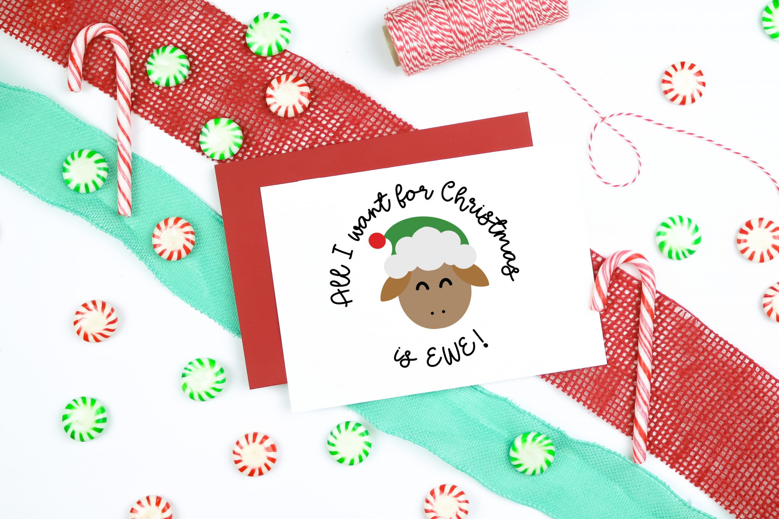 All I Want for Christmas is EWE SVG design on a christmas card with ribbon, candy, and twine