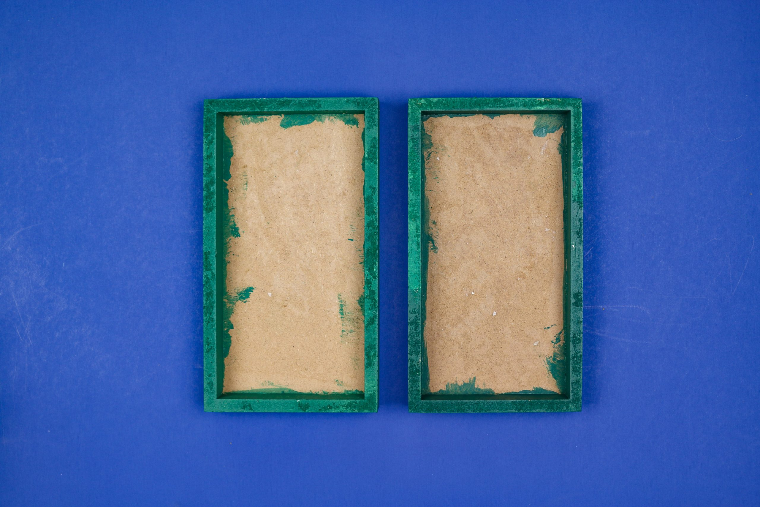 unfinished Green painted frames on a blue background