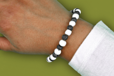 woman's wrist wearing black and white bug repelling bead bracelet