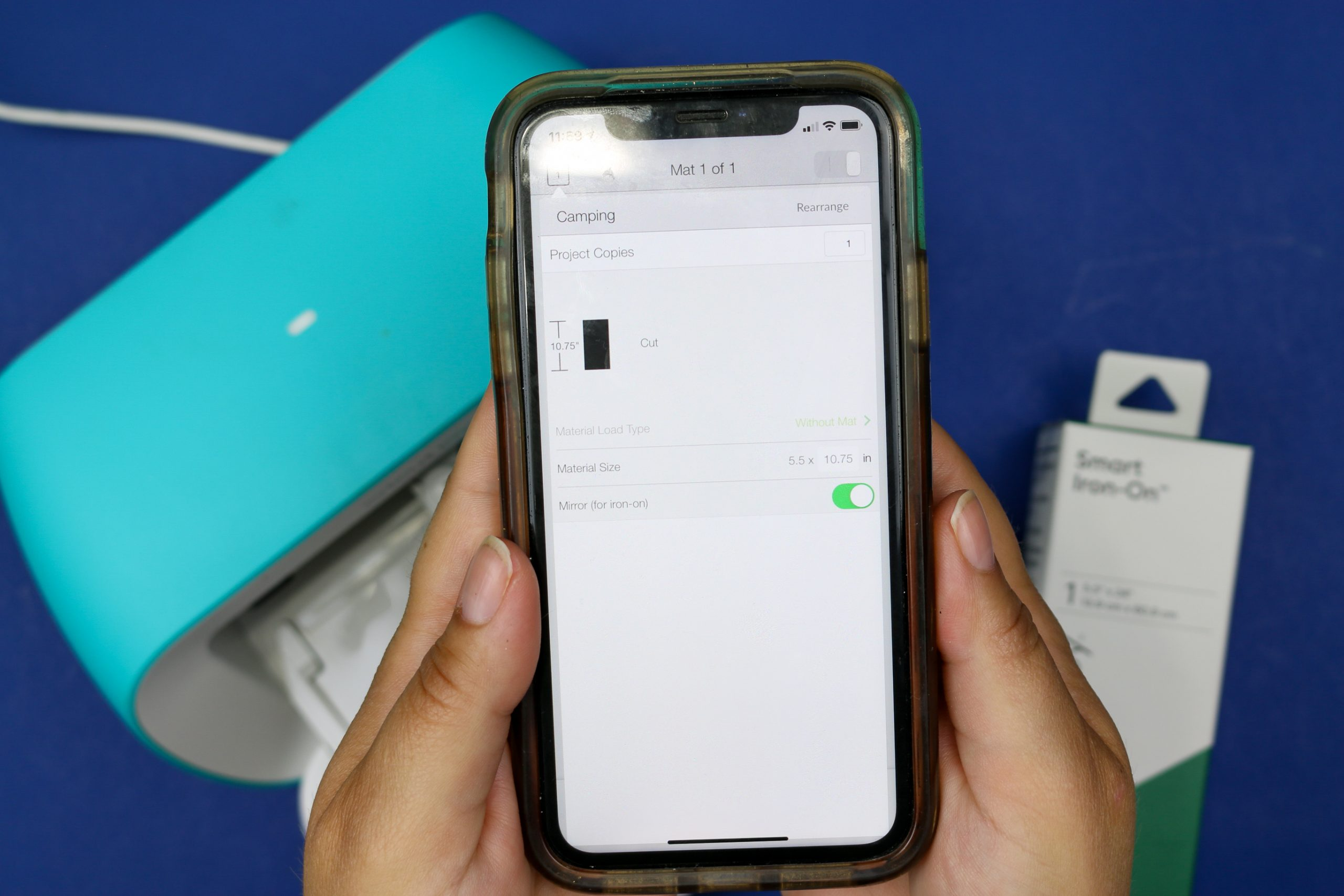 hands holding a smart phone displaying Cricut Design Space's mirror function