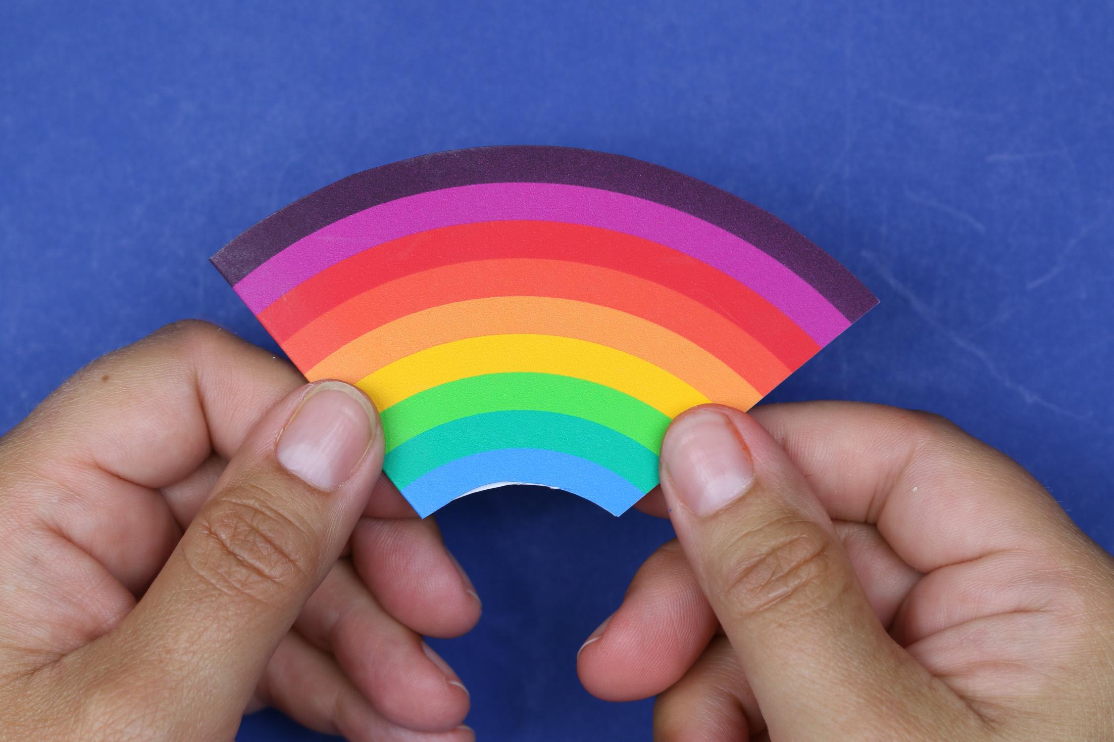 hands holding a rainbow corner bookmark