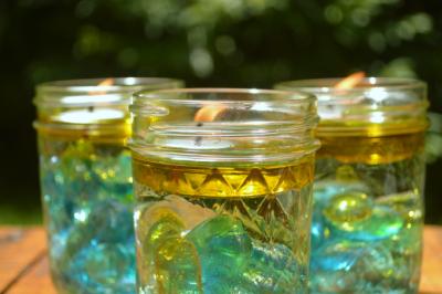 three citronella candles in mason jars