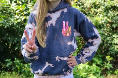 girl wearing bleach dyed sweatshirt and giving the peace sign