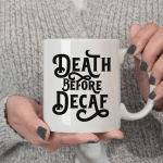 white womans hand holding a mug that reads Death Before Decaf