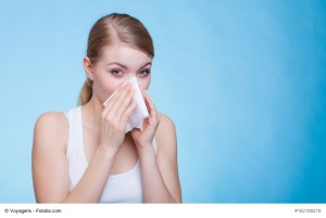 woman holding tissue to nose