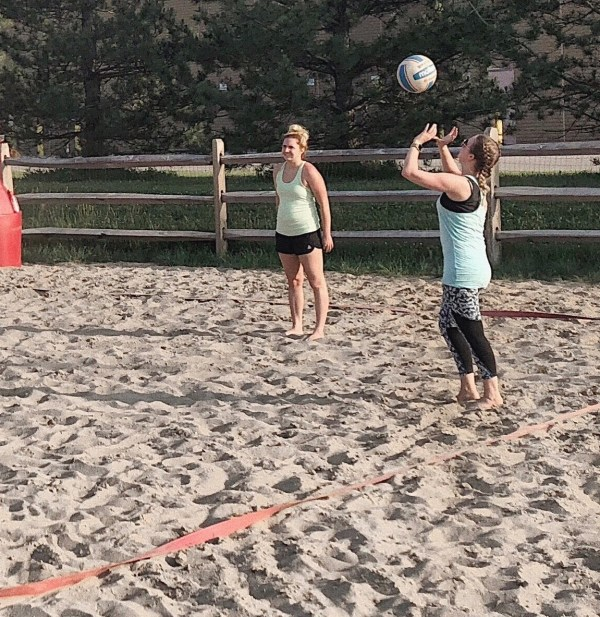 Madison playing sand volleyball outdoor one year ago, showing her body change