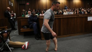 Paralympic gold medalist Oscar Pistorius prepares to walk across the courtroom without his prosthetic legs during the third day of his hearing at the Pretoria High Court for sentencing procedures in his murder trial in Pretoria on June 15, 2016. The final witness was due to appear at Oscar Pistorius's sentencing hearing on June 15 as the paralympic athlete awaits a new jail term for murdering his girlfriend Reeva Steenkamp three years ago. / AFP PHOTO / POOL AND AFP PHOTO / SIPHIWE SIBEKO