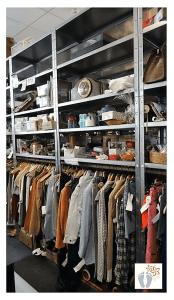 """Im Second-Hand-Geschäft """"Konsumreform Shop"""" in Essen (Deutschland): Reihe, bestehend aus Regalen mit je drei Fachböden und einer Kleiderstange."""