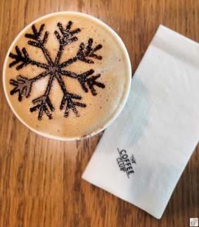 """Tasse Cappuccino mit Kakao-Art - und eine Serviette mit dem Textlogo """"The Coffee Club"""""""