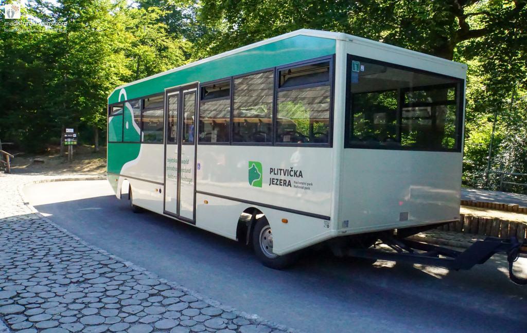 """hinterer Teil des Panoramazuges (eher Bus, ähnlich einem Sattelauflieger); im Hintergrund des Bildes Bäume und kaum erkennbare Wegweiser; links oben Text """"mado-unterwegs.com"""""""