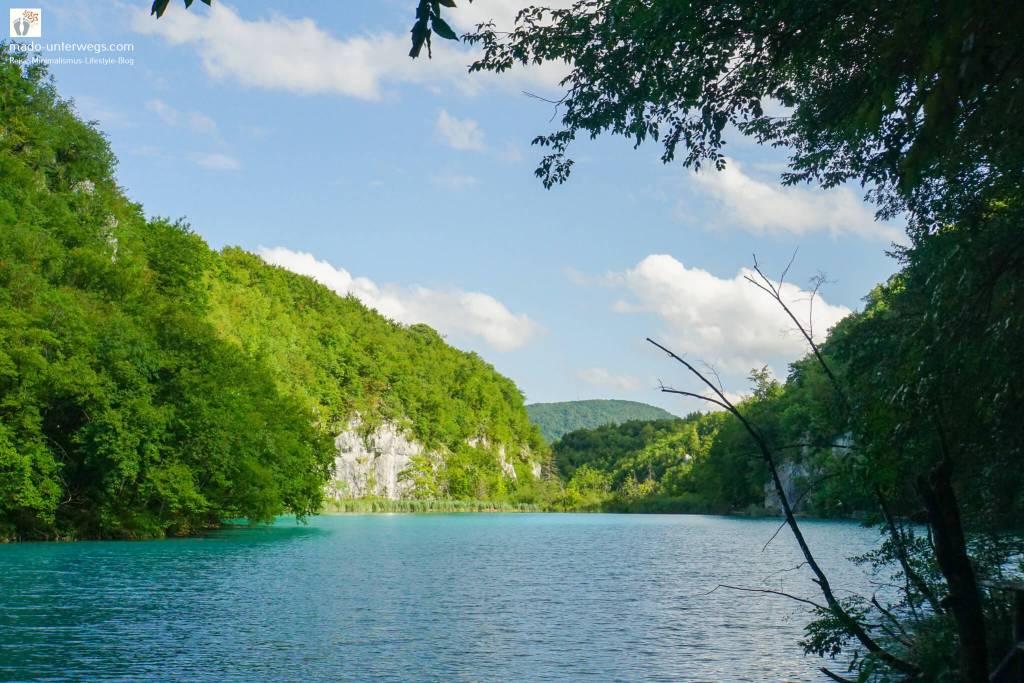 """Ausblick auf einen See im Nationalpark Plitvicer Seen - Kroatien   auf der rechten Seite des Bildes ein Baum, der in die Mitte hineinragt und eher im Schatten liegt; links bis in den Hintergrund von der Sonne beleuchtete Pflanzenwelt; am Himmel ein paar Wölkchen; links oben Text """"mado-unterwegs.com"""""""