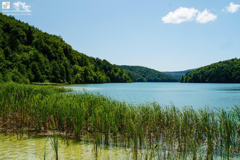 """Ausblick auf einen See im Nationalpark Plitvicer Seen - Kroatien   auf der linken Seite des Bildes bewaldete Berge; in der Mitte des Bildes bis zur rechten Seite See mit Gräsern am Uferrand; links oben Text """"mado-unterwegs.com"""""""