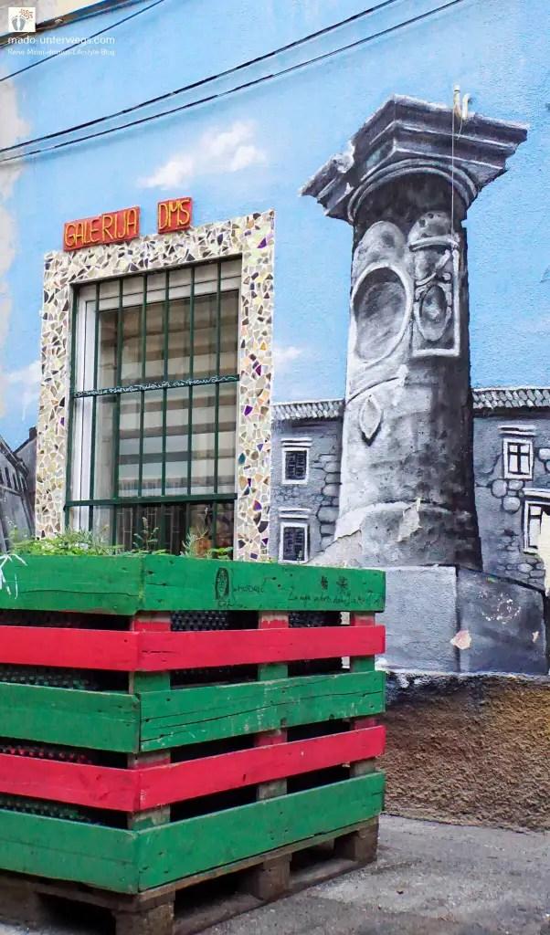 """Hochbeet aus farbigen Paletten, im Hintergrund ein vergittertes Fenster und Street-Art: Säule – in Rijeka - Kroatien / links oben der Text """"mado-unterwegs.com"""""""