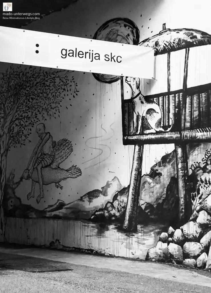 """Schild mit dem Text """"Galerija Skc"""", im Hintergrund Street-Art: Hund auf einer Plattform mit Sonnenschirm, Mond, Baum, Vogel – in Rijeka - Kroatien / links oben der Text """"mado-unterwegs.com"""""""