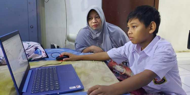 Jumini. L, orang tua murid di Depok mendampingi anak dalam pembelajaran daring, Rabu (13/8). (Dok. Lintang Dyah Ramadhani)