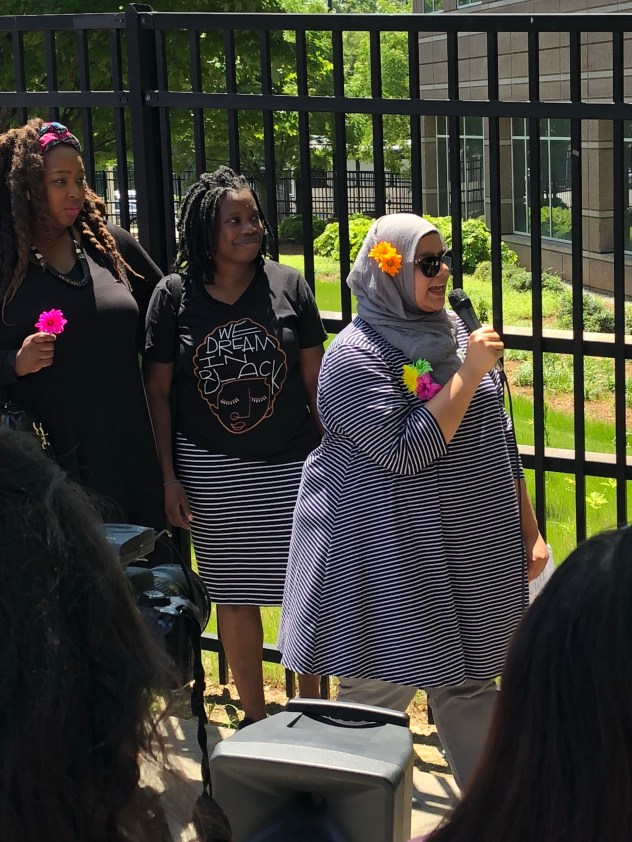 Woman in shawl and head covered and flower on head speaks into microphone in front of fence