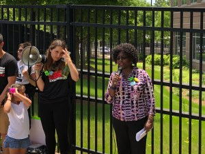 african woman with microphone stands in front of fence next to another woman holding bullhorn