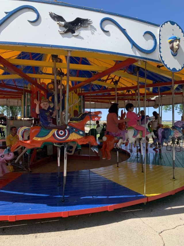 child waving from carousel