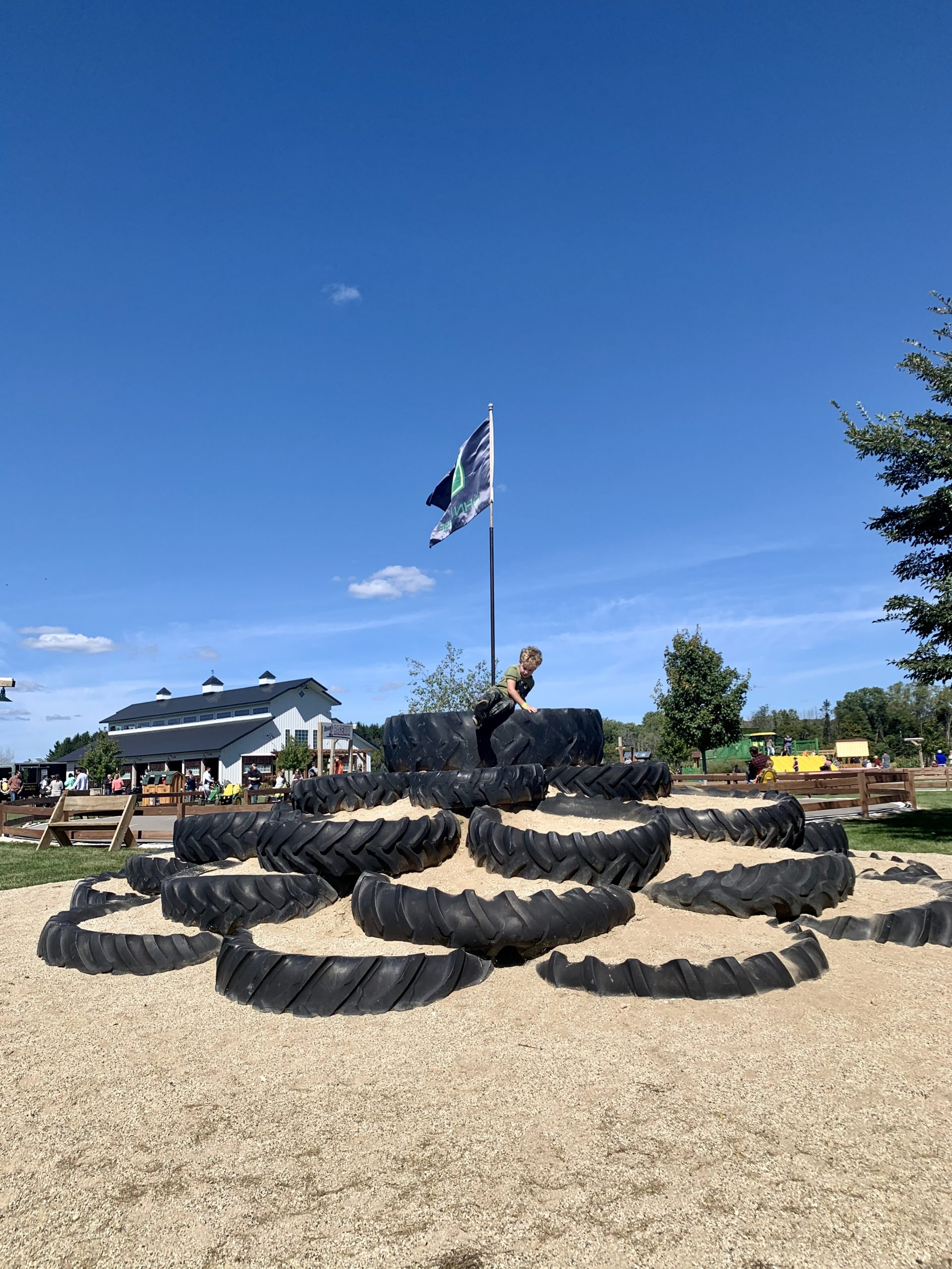 Kid climbing a giant tire mountain at Basse's