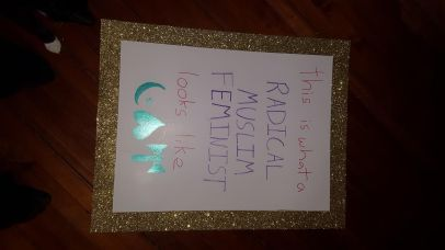 """A sign with gold glitter around the border and the text """"this is what a RADICAL MUSLIM FEMINIST looks like."""" A crescent and star, heart pointing up, and labrys are drawn in green at the bottom."""