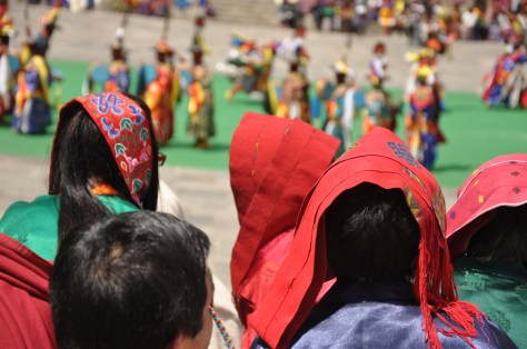 Bhutanese women covering their hair from hot sun while watching the tsechu.