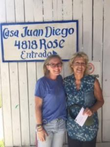 "Janet Lowery and Meg Spesia smile for the camera under a blue and white sign reading ""Casa Juan Diego 4818 Rose Entrada"""