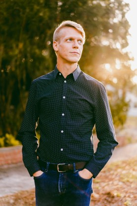 Author and journalist, Cooper Levey-Baker. He has blond hair and is standing wearing a dark button-up shirt and jeans. There are trees with sunlight filtering through them in the background.