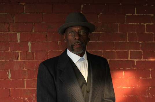 Author Earl S. Braggs stands with a red brick wall at his back. He is an African American man wearing a Trilby hat, a vest and jacket and a white shirt. He wears wire-rimmed glasses.