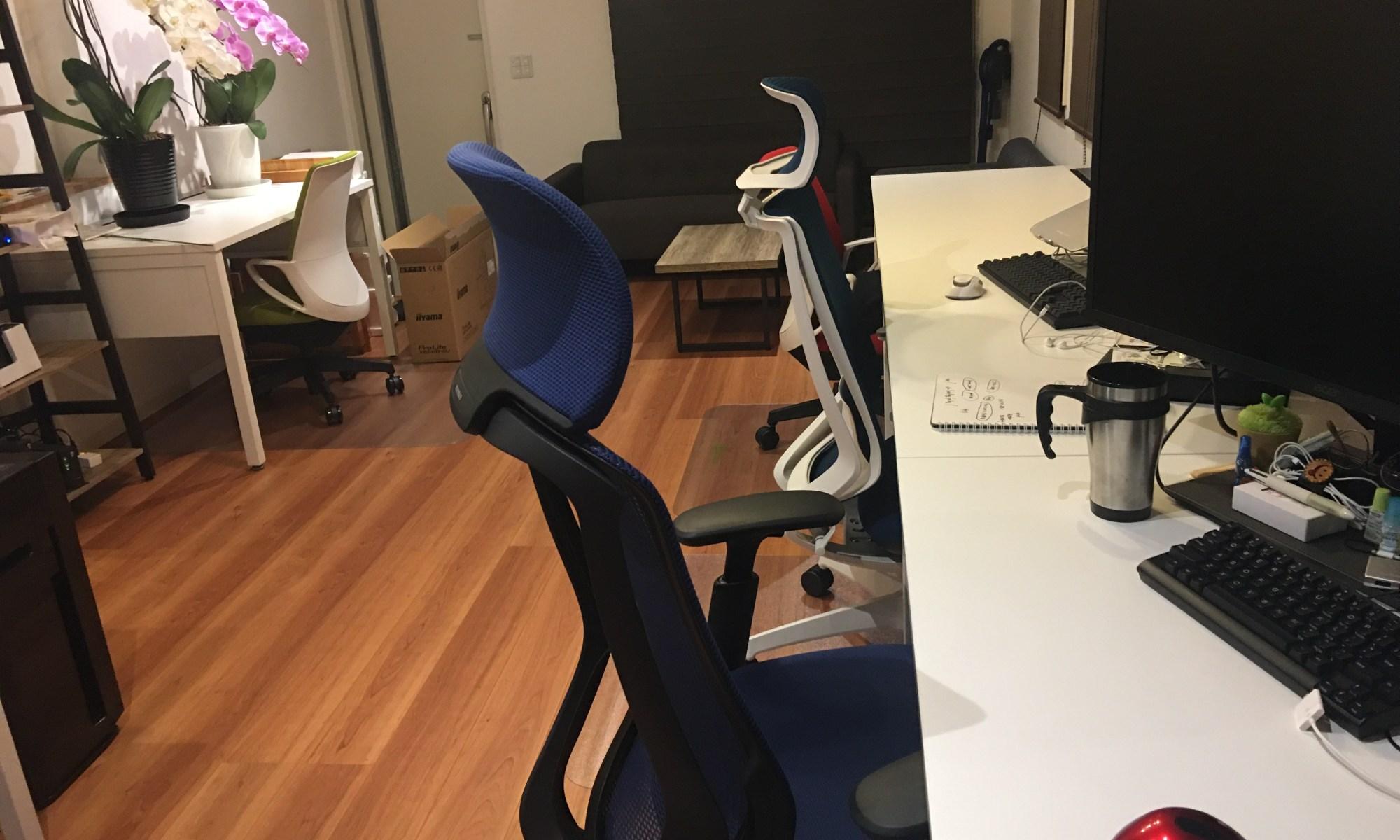 写真:室内。椅子が3脚と机、ディスプレイ、玄関付近に白とピンクの胡蝶蘭が飾っている。