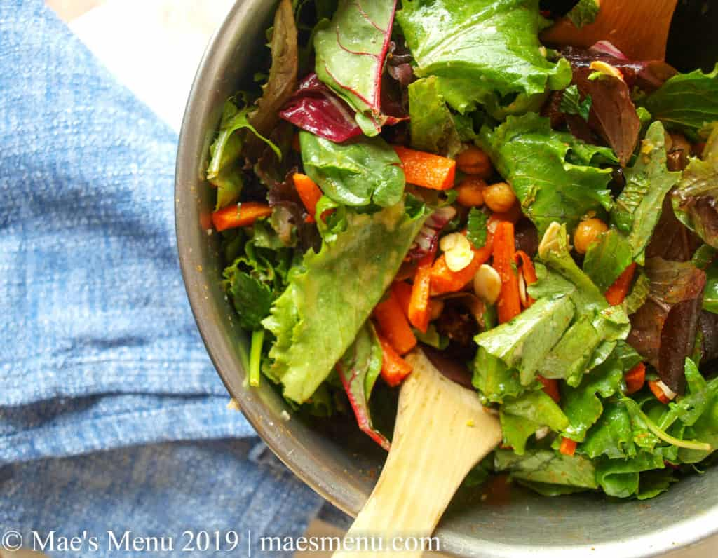 Tossed green salad with almonds, chickpeas, carrots, dressing, and wooden salad tongs in metal bowl. Blue dish towel to the left of bowl.