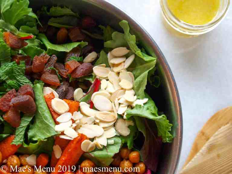 Metal bowl of green salad with chickpeas, carrots, almonds, and chopped dried apricots. Salad tongs and lemon dressing next to the bowl on the white counter.