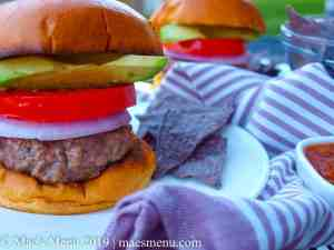 Two tall burgers with blue corn tortilla chips and a purple striped dish towel.