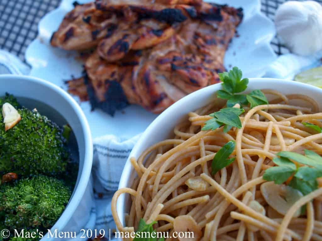 Plate of grilled chicken thighs, a bowl of garlic spaghetti, and a dish of roast broccoli all sitting on a striped white dish towel.