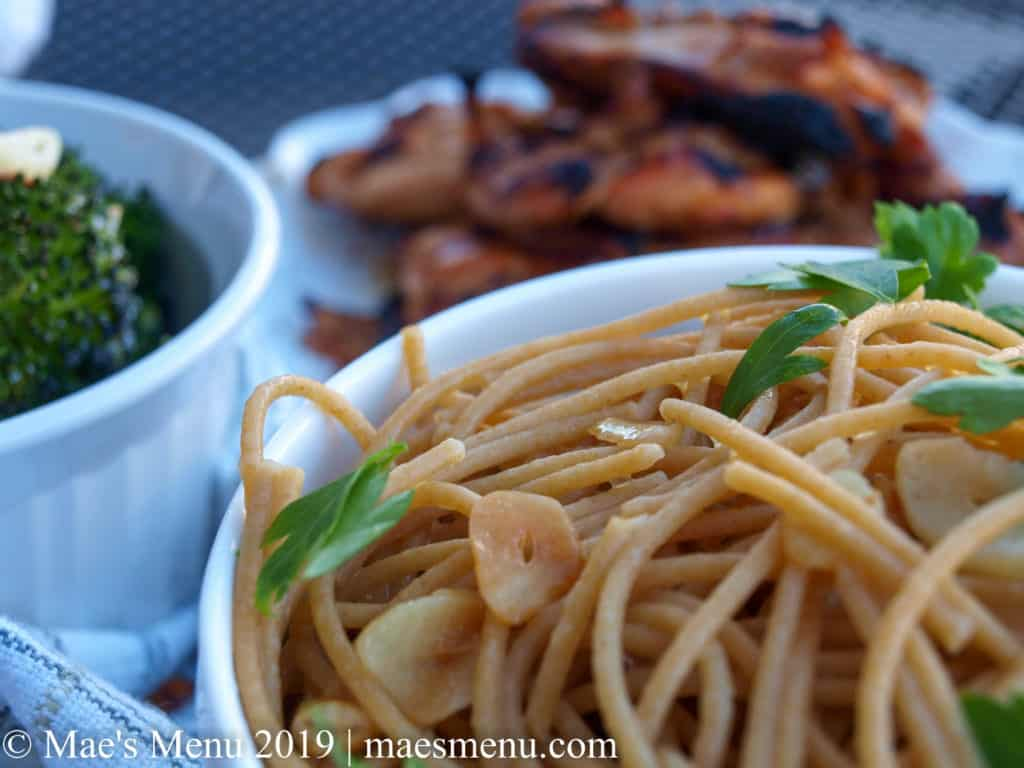 Spaghetti with stir fried garlic and parsley next to a white bowl of broccoli and grilled sesame chicken thighs.