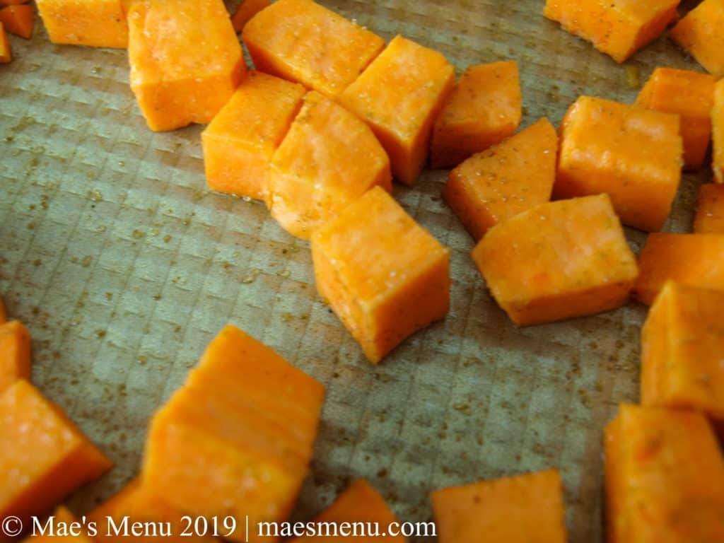 Seasoned cubed sweet potato chunks on an oiled gold baking sheet.