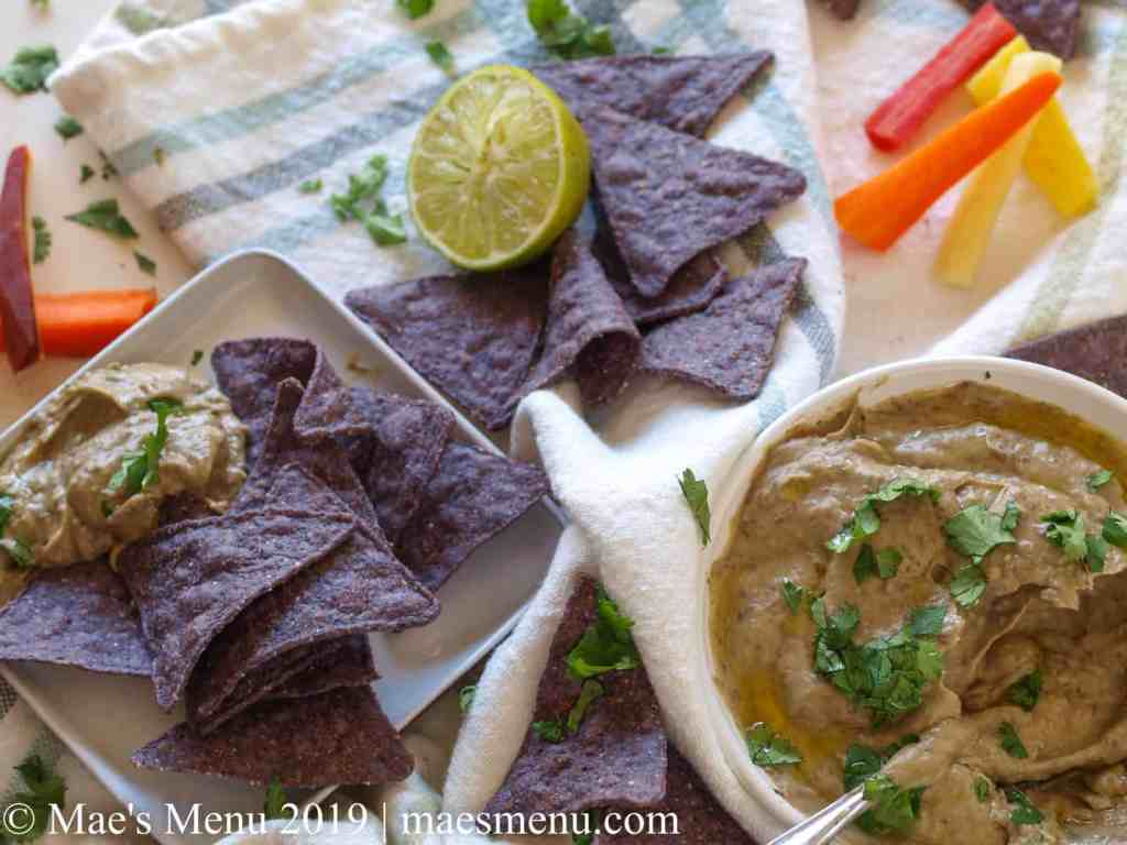 Purple tortilla chips, carrots, cilantro, and half a lime sit on white striped dish towel next to a white crock of Creamy Avocado Black Bean Dip.